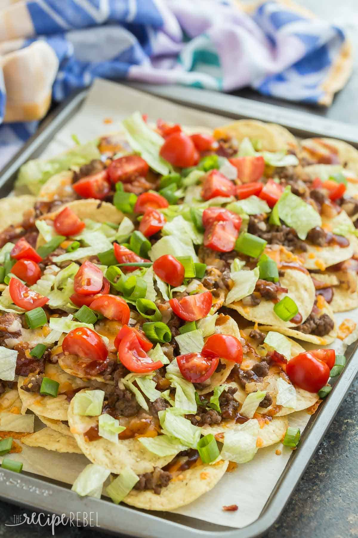 BBQ Bacon Cheeseburger Nachos are the best BBQ nachos you've ever had! Barbecue sauce, ground beef, bacon, cheddar cheese, green onions and all the burger toppings you want. Perfect for movie night or game day! Includes step by step RECIPE VIDEO. #nachos #appetizer #groundbeef #beef #recipe #recipes