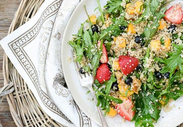 berry arugula salad with quinoa on a white plate