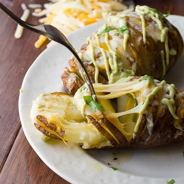 cheesy jalapeno hasselback potatoes on white plate with fork pulling potato apart