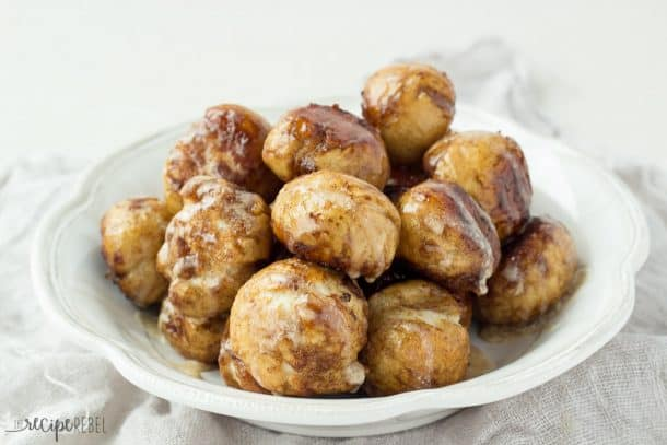 white bowl filled with cinnamon sugar coated pretzel bites drizzled with glaze