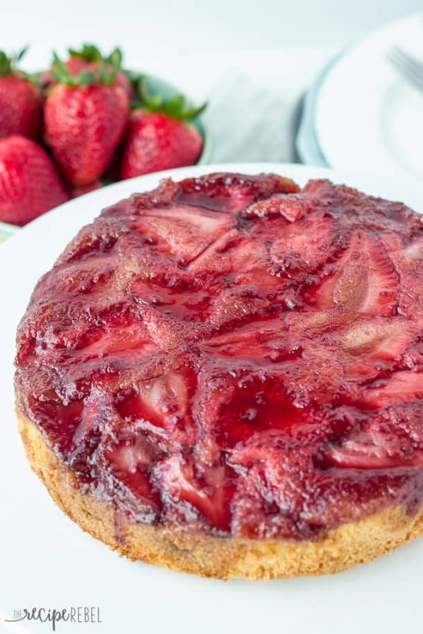 whole strawberry upside down cake with berries on top on a white plate