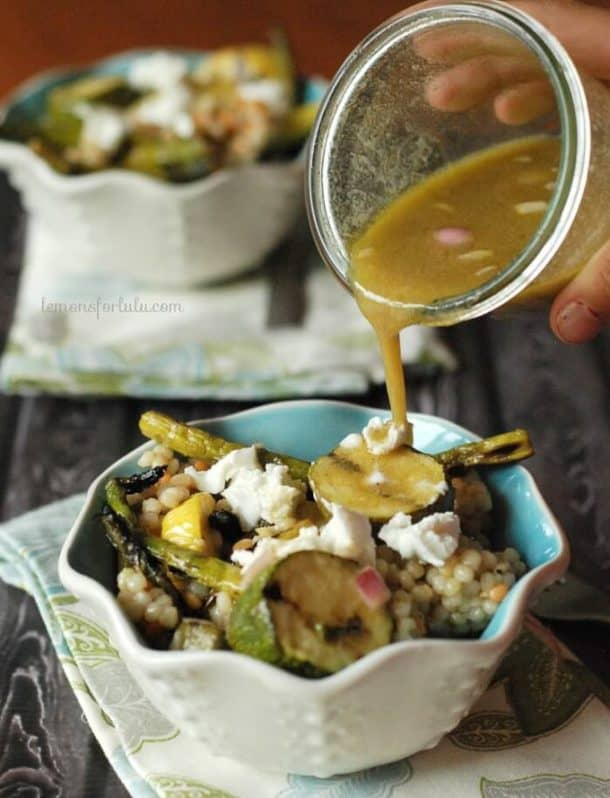 grilled veggies couscous salad in white and blue bowl with dressing being poured on