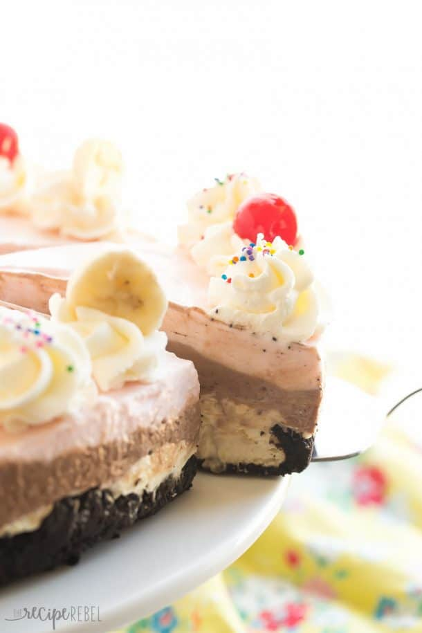 no bake banana split cheesecake with three layers and whipped cream maraschino cherries banana slices and sprinkles on top