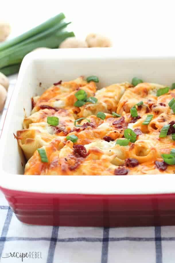 Perogy Stuffed Shells: garlic herb mashed potatoes and cheddar cheese stuffed inside a large pasta shell, and topped with creamy Béchamel sauce, more cheddar cheese and bacon before baking. An indulgent, make-ahead side dish that's perfect for leftover mashed potatoes! www.thereciperebel.com