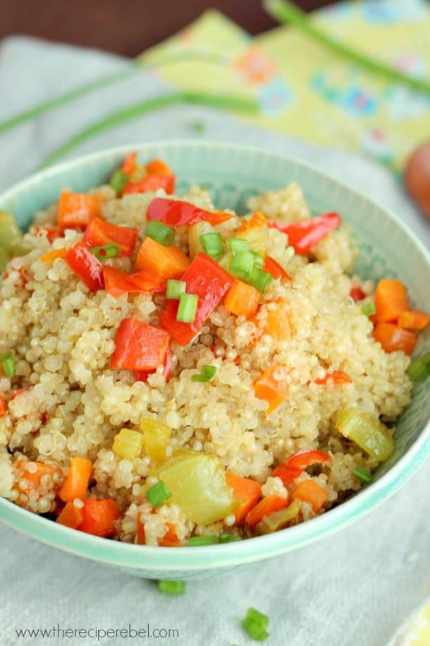 quinoa pilaf in blue bowl with peppers and green onions on top