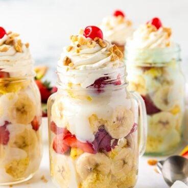 banana split trifle in mason jar with whipped cream