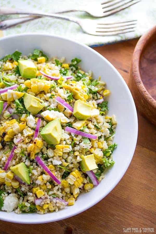 charred corn salad with avocado and red onion in white bowl