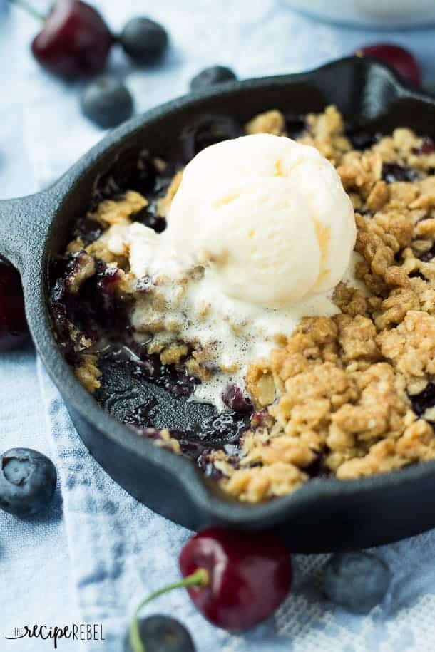 berry cherry crisp in cast iron skillet with scoop of vanilla ice cream melting on top