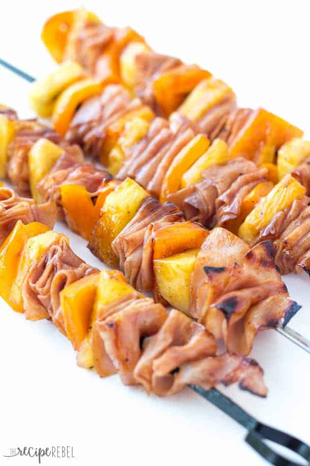strips of ham pineapple chunks and peppers on metal skewers grilled with sauce