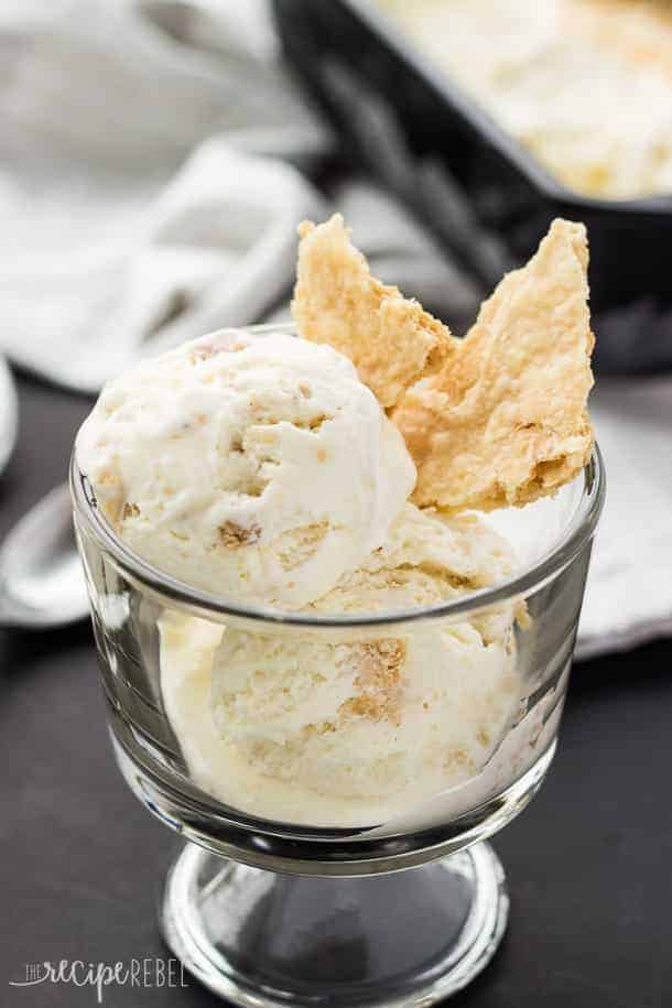 two scoops of coconut cream pie ice cream in glass bowl with pieces of pie crust stuck in the side