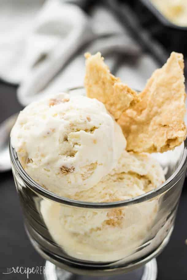 close up of scoops of coconut cream pie ice cream in bowl with chunks of pie crust