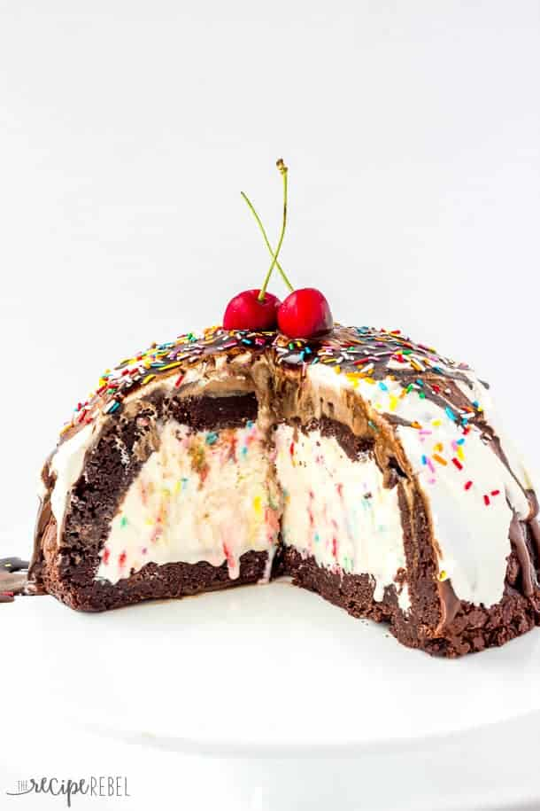 Ice Cream Brownie Mountain: A fun new ice cream cake! Rich, fudgy brownies filled with homemade ice cream (or use store bough and keep it simple!) and topped with chocolate ganache, whipped cream, chocolate sauce and sprinkles -- the perfect cake for a birthday or celebration! Change up the ice cream flavors to suit your tastes! www.thereciperebel.com