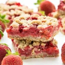 Strawberry Rhubarb Crisp Bars: Oatmeal cookie base topped with sweet and tangy strawberries and rhubarb topped with more oatmeal cookie topping -- your favorite summer dessert is now a portable treat or back to school snack! www.thereciperebel.com