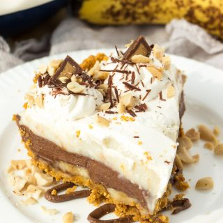 A peanut butter graham cracker crust filled with bananas, Reese's spread, vanilla pudding and whipped cream, topped with peanut butter cups, chocolate shavings and salted peanuts -- the best banana cream pie you'll ever have!