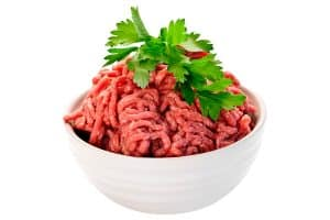 image of a white bowl filled with raw ground beef and parsley on top
