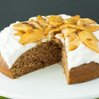 A moist spice cake made healthier with applesauce, whole wheat flour and reduced sugar, topped with whipped cream and caramelized apples -- the perfect holiday treat!