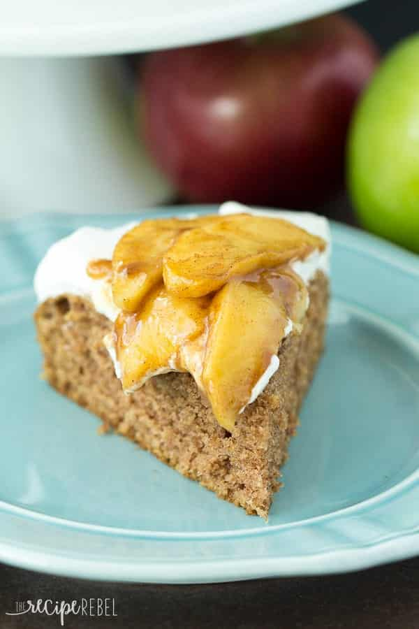 slice of apple spice cake on blue plate topped with whipped cream and sauteed apples