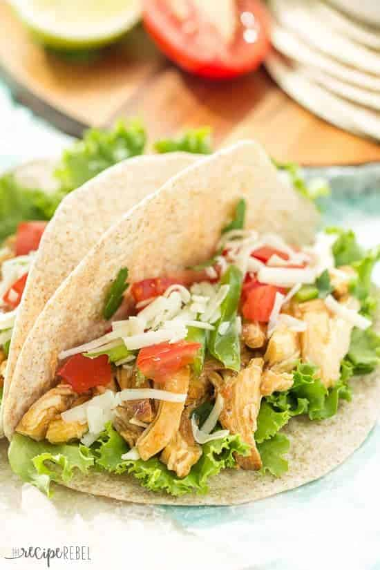 honey sriracha shredded chicken tacos in flour tortillas with lettuce tomatoes and cheese