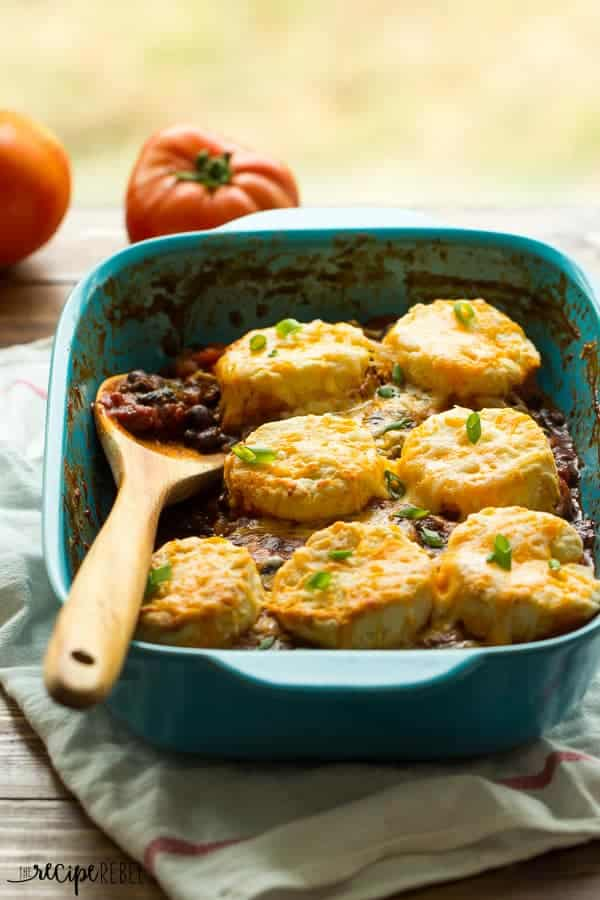 bright blue baking dish with chili and a layer of biscuits on top topped with cheese