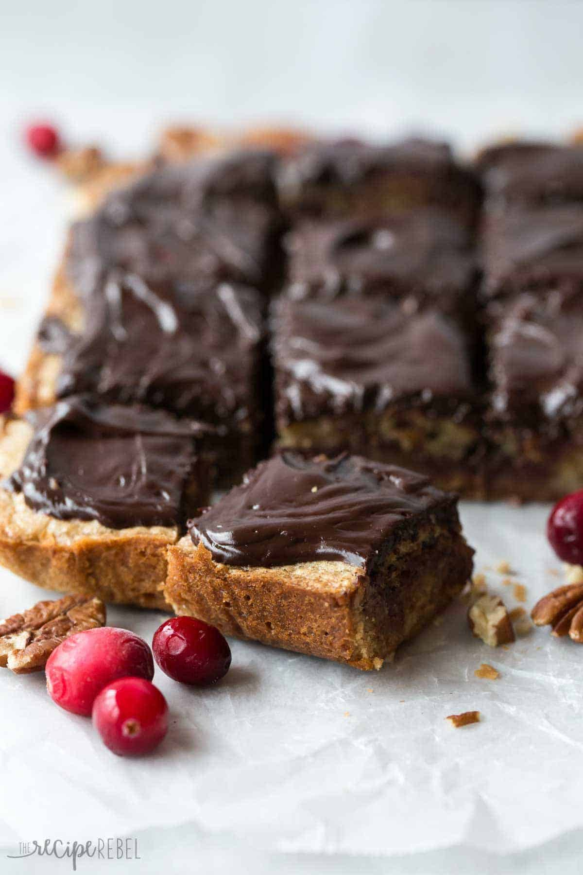 close up image of dark chocolate cranberry blondies cut into squares on parchment paper