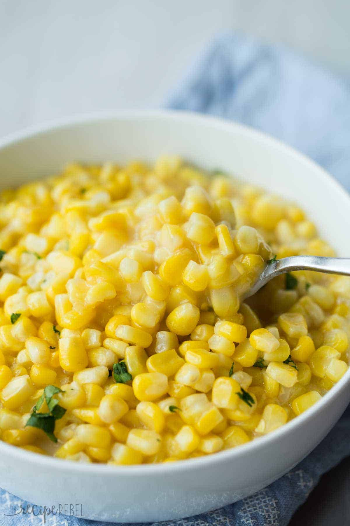 close up of white bowl with spoon scooping cream corn