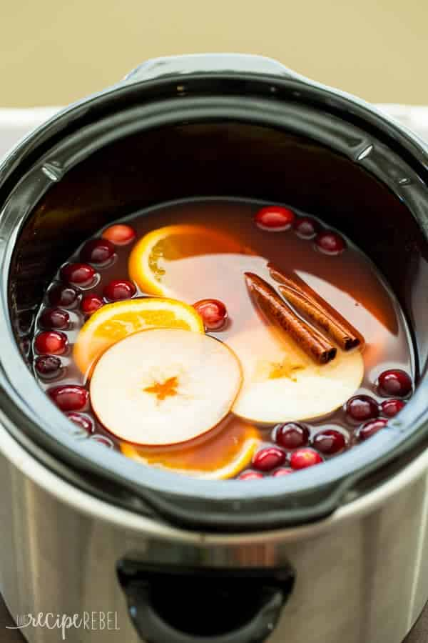 slow cooker cranberry apple cider in black crockpot with apple slices orange slices cinnamon sticks and cranberries