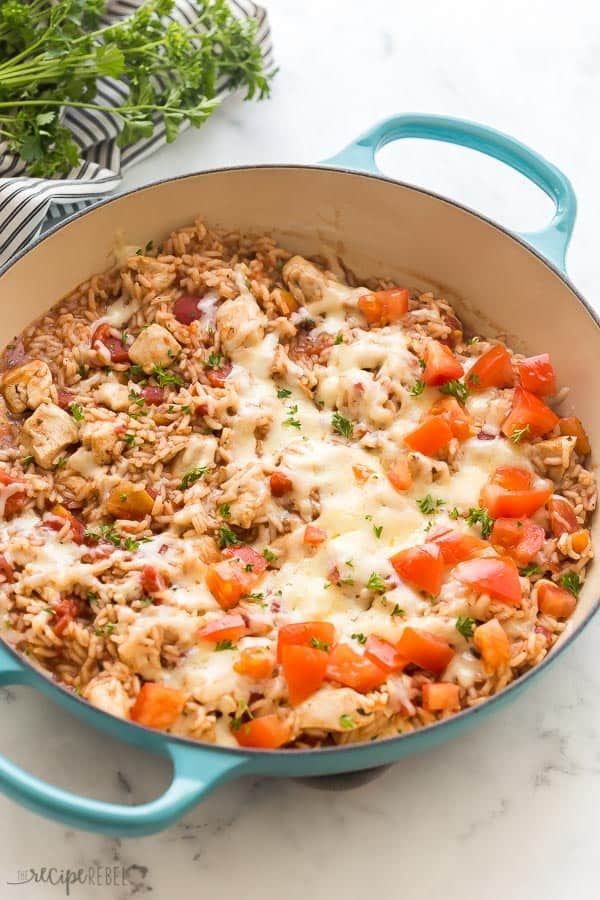 caprese chicken and rice in one pot blue braiser with fresh tomatoes