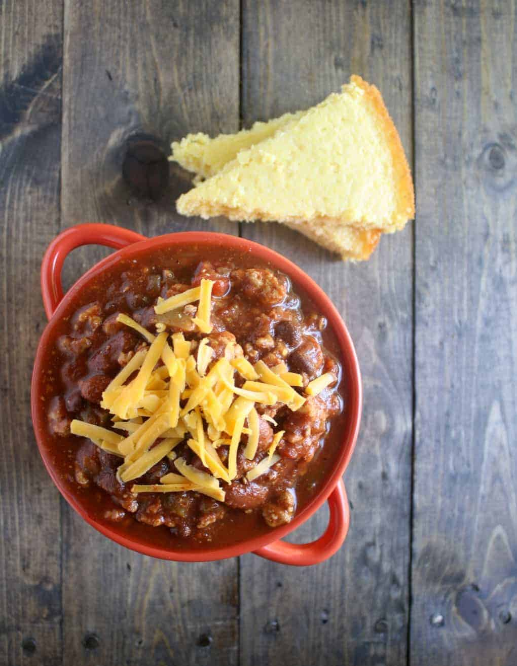 crockpot turkey chili overhead in red bowl on wooden background