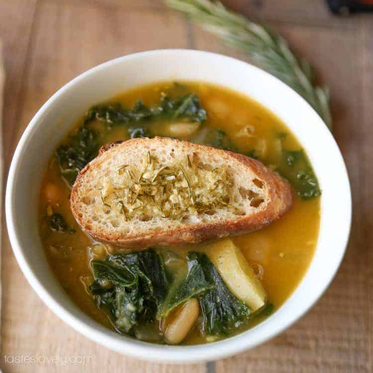 potato white bean kale soup with crusty bread on top in soup