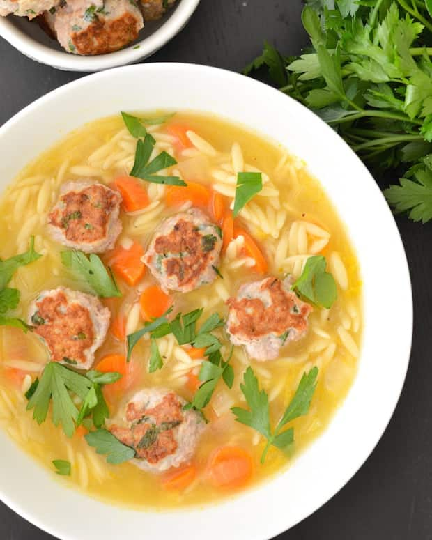lemon orzo soup with turkey meatballs in white bowl with carrots and parsley