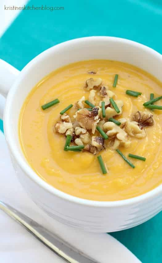 butternut squash soup in white bowl topped with walnuts and chives