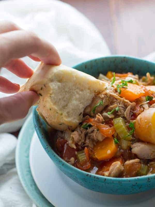 slow cooker tuscan chicken stew in bright blue bowl with crusty bread dipping in