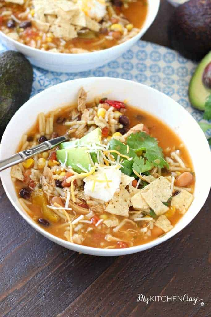 taco soup in white bowl topped with sour cream cheese and avocado