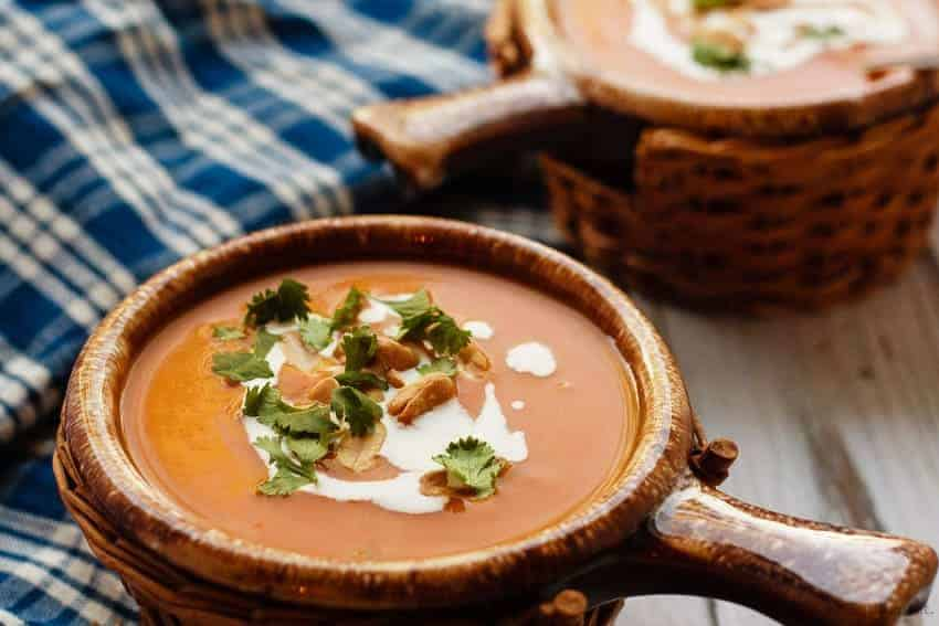 slow cooker thai pumpkin soup in brown bowls with blue plaid napkin behind