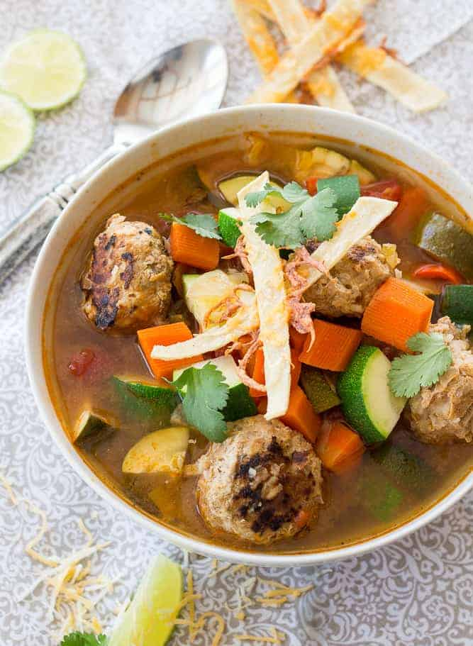 mexican meatball soup topped with tortilla strips and cilantro