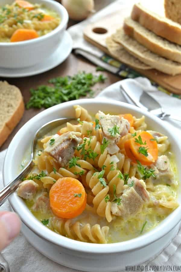 creamy chicken noodle soup in white bowl piled high with noodles chicken and carrots