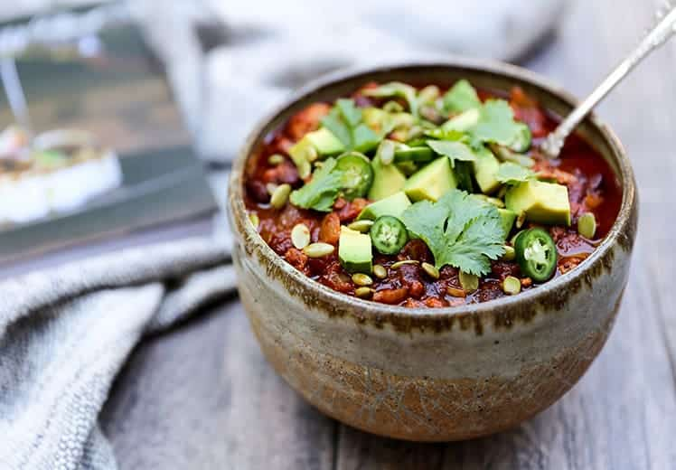 turkey chili in grey bowl with jalapenos cilantro and avocado on top