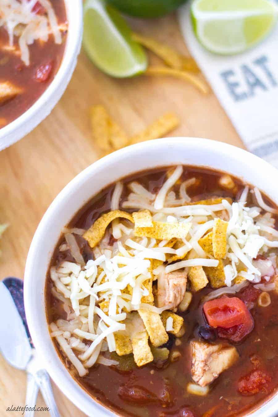 chicken tortilla soup overhead in white bowl with tortilla strips and cheese