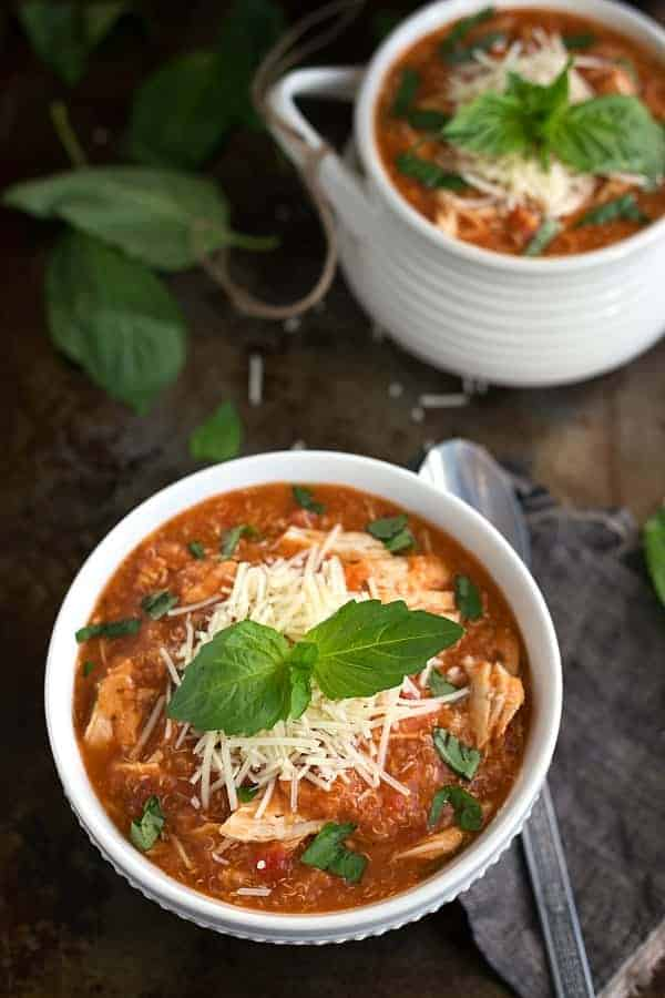 slow cooker chicken parmesan quinoa soup in white bowl topped with parmesan cheese and basil