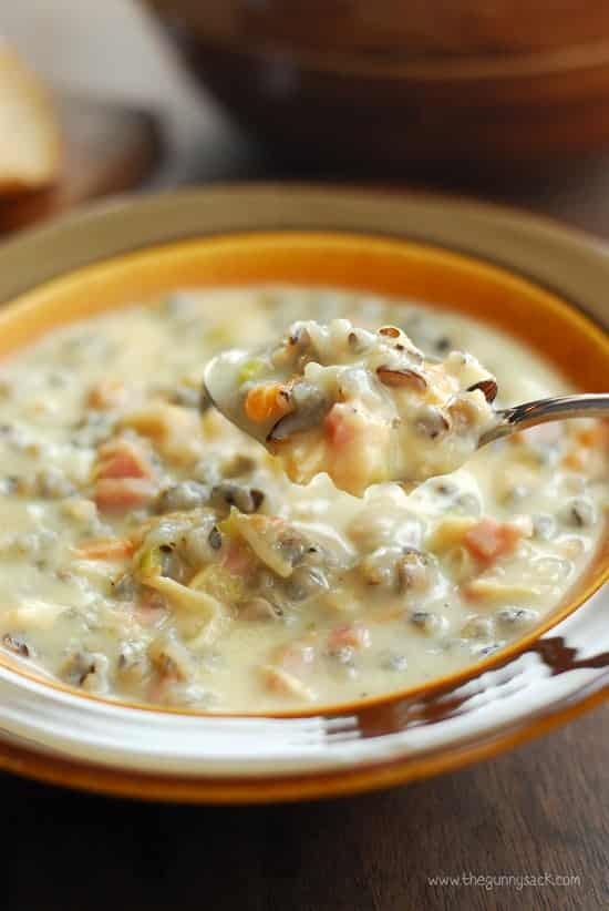 creamy chicken wild rice soup in brown bowl with spoon scooping bite