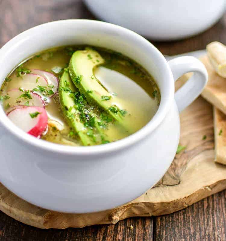 chicken posole verde soup in white bowl with avocado slices and radishes