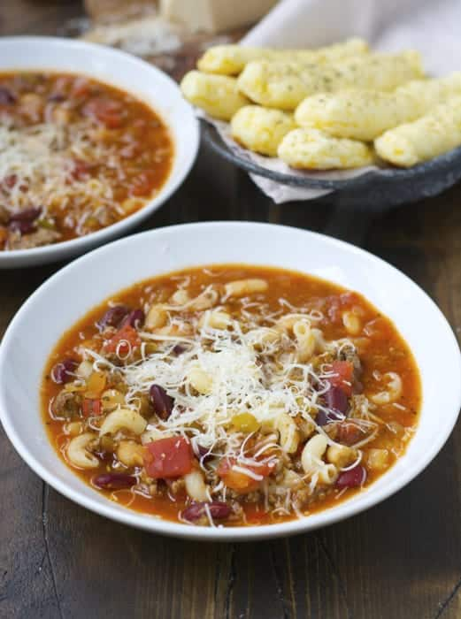 slow cooker pasta fagioli in white bowl topped with shredded parmesan