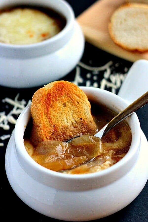 french onion soup in white bowl with crusty bread in the side