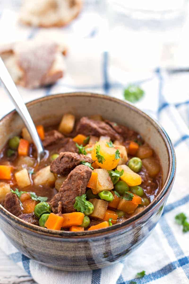 simple beef stew in brown bowl with spoon stuck in soup