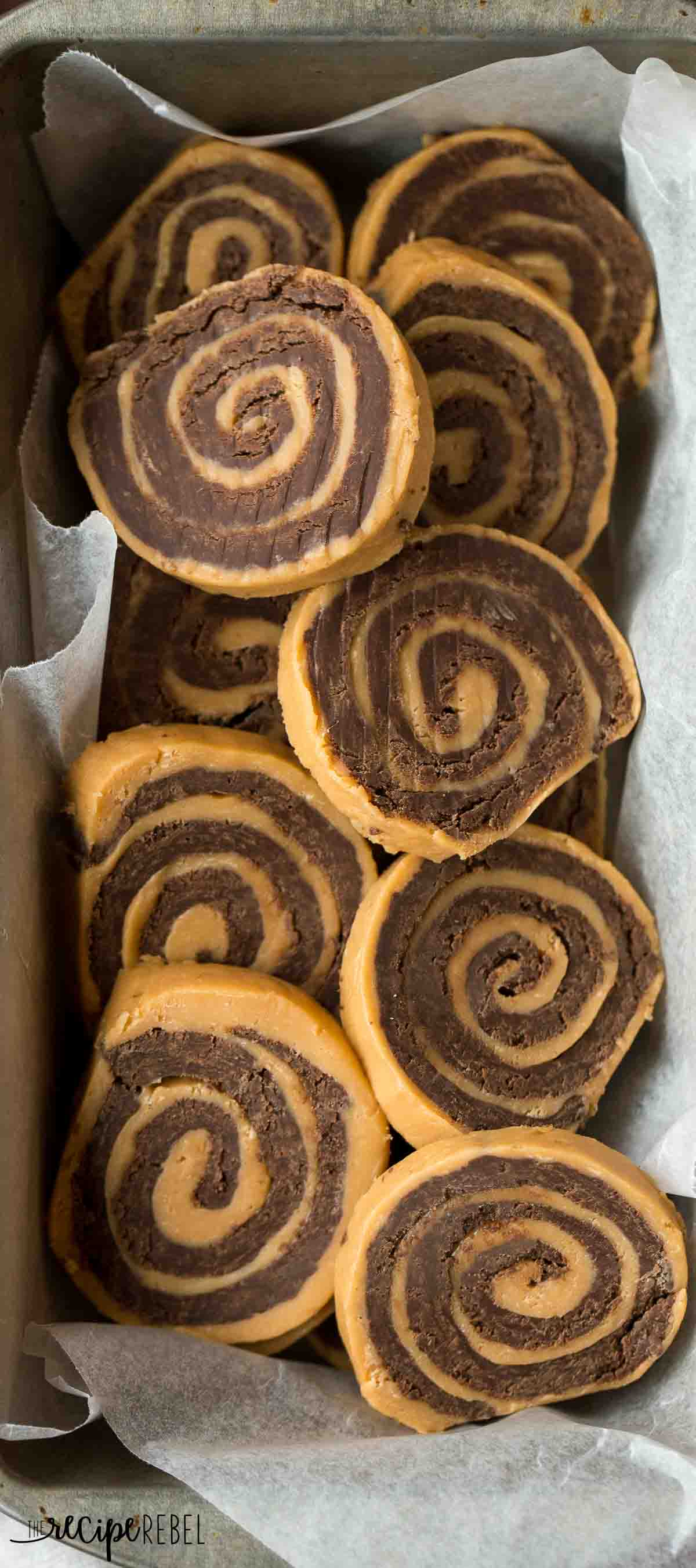 slices of chocolate peanut butter pinwheels stacked in loaf pan on parchment paper