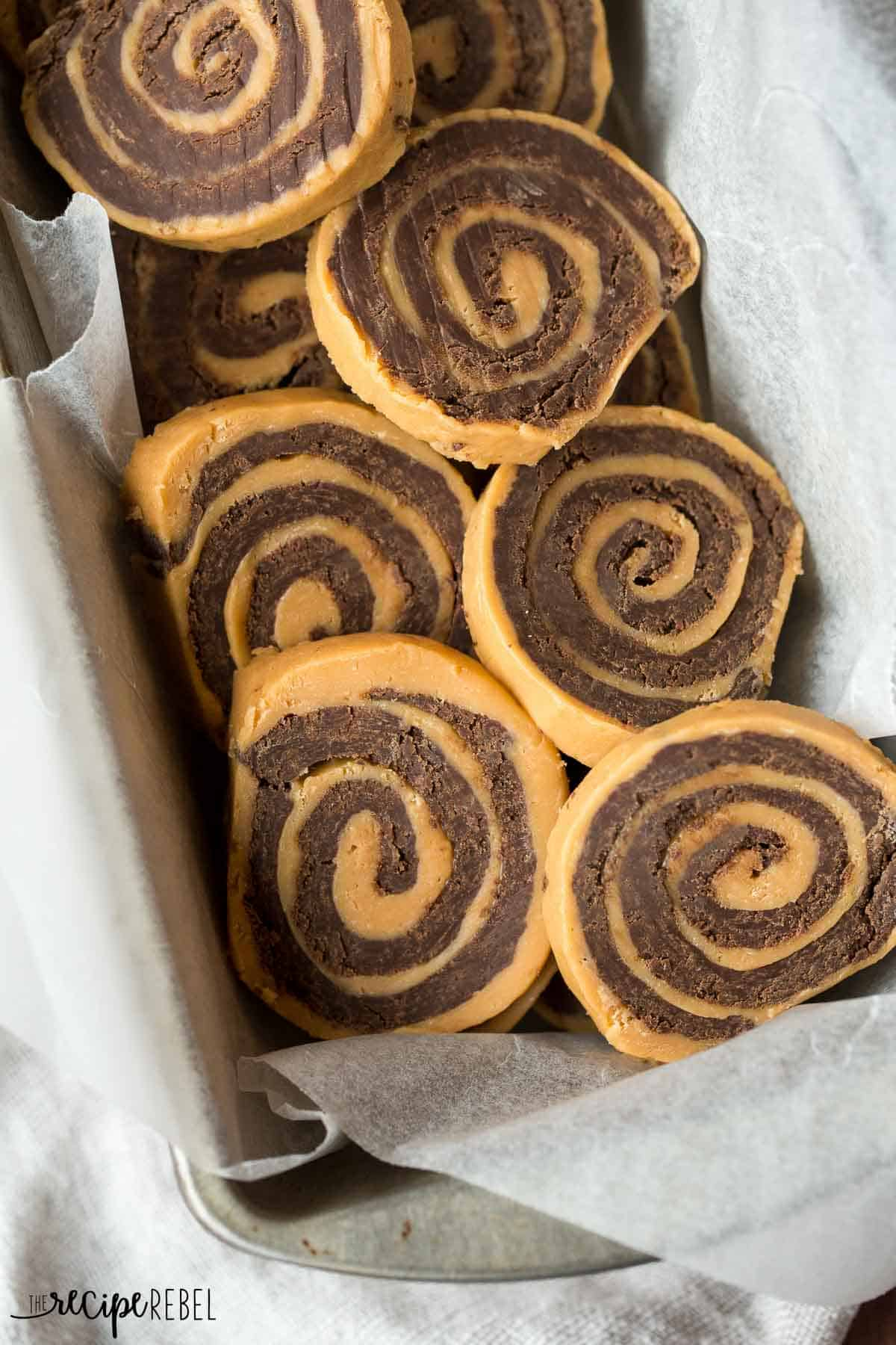 chocolate peanut butter pinwheels in a loaf pan lined with parchment paper