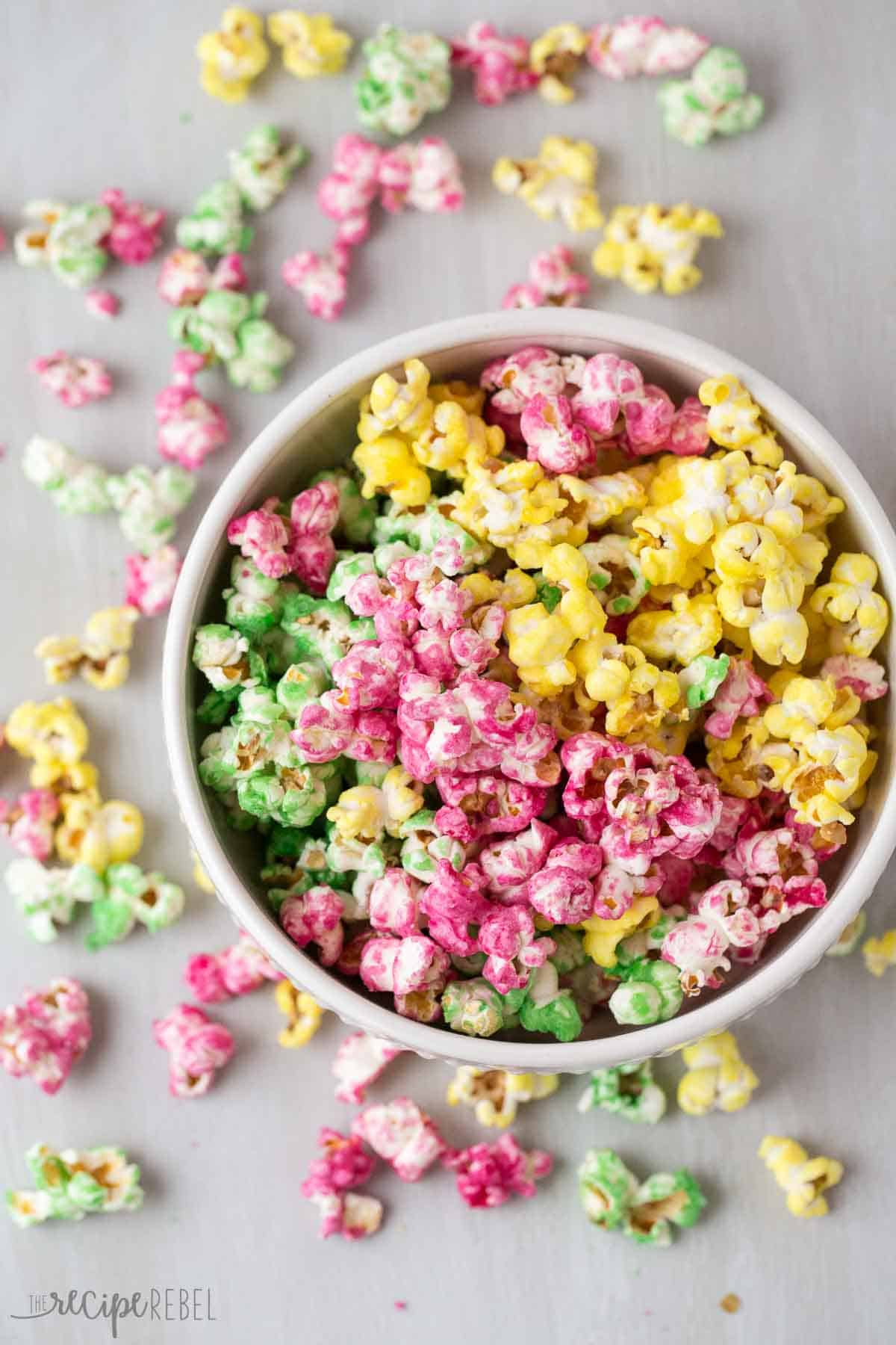 candy popcorn in pink green and yellow in white bowl on a grey background