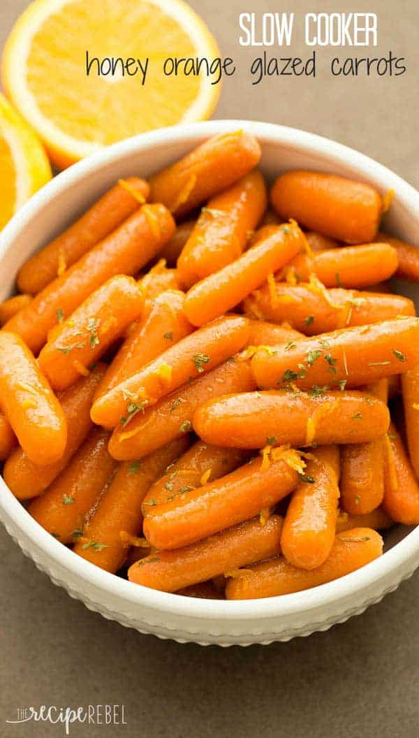 slow cooker honey orange glazed carrots in white bowl with orange zest and parsley on top