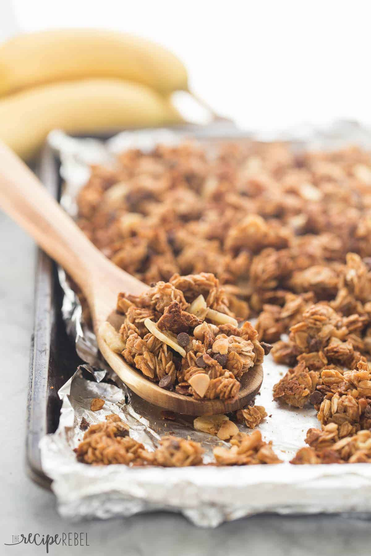 chunky monkey granola baked on a sheet pan lined with foil and some in a wooden spoon