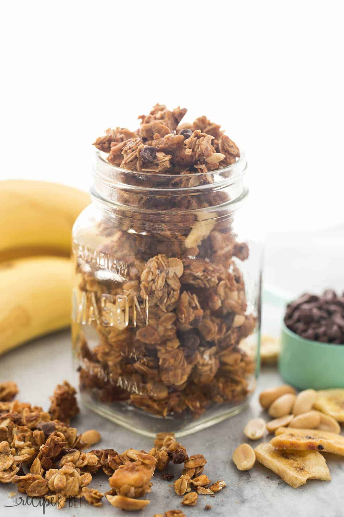chocolate peanut butter granola in glass mason jar with bananas in the background